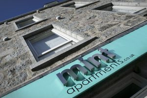 Mint Apartments Aberdeen - sign looking up